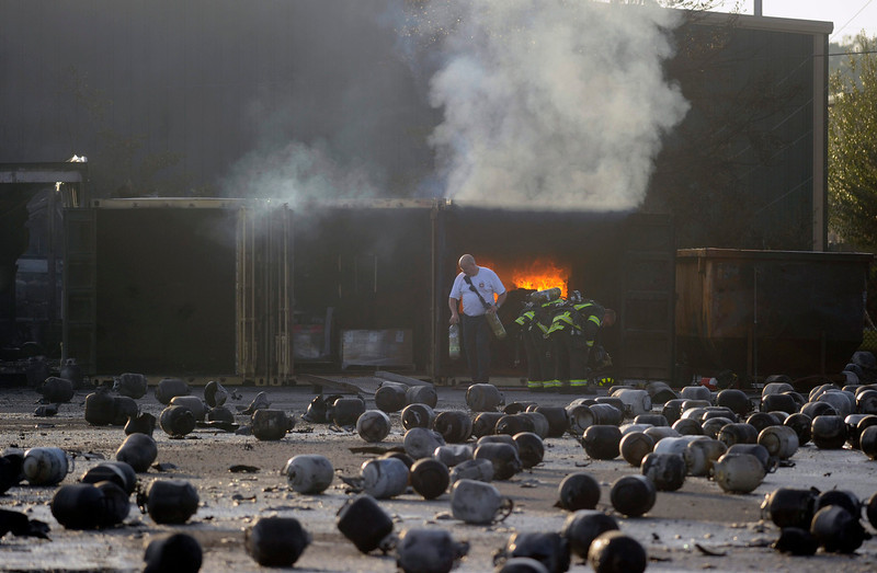 . Firefighters prepare to put out a container of burning caps, as thousands of exploded propane cylinders litter the storage yard of a propane plant, after massive explosions overnight in the plant\'s yard, in Tavares, Florida, July 30, 2013. Dozens of explosions rocked a propane tank servicing plant in central Florida, northwest of Orlando, late on Monday, injuring seven workers, at least three critically, and prompting the evacuation of nearby homes, authorities said.    REUTERS/David Manning