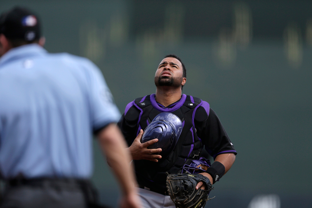 . Colorado Rockies catcher Wilin Rosario looks skyward before starting the first inning of a spring training baseball game against the Arizona Diamondbacks, Friday, Feb. 28, 2014, in Scottsdale, Ariz. (AP Photo/Gregory Bull)