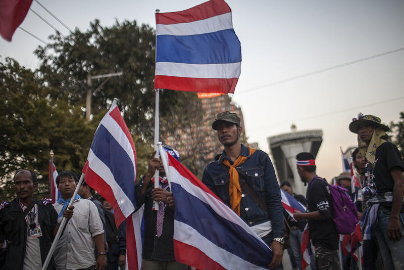 """. Thai anti-government protesters hold national flags as they start massing at one of their designated sites in a move to \'shut down\' Bangkok on January 12, 2013.  Thai anti-government protesters are vowing to \""""shut down\"""" Bangkok on January 13 in an effort to prevent upcoming elections and topple the government as the country\'s political crisis teeters on the brink of a tumultuous new phase.  (KC Ortiz/AFP/Getty Images)"""