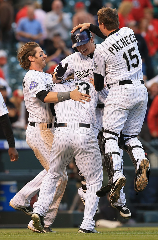 . Corey Dickerson #6 of the Colorado Rockies is mobbed by teammates Charlie Blackmon #19, Charlie Culberson #23 and Jordan Pacheco #15 as they celebrate his RBI triple that scored DJ LeMahieu #9 of the Colorado Rockies for the game winning run against the St. Louis Cardinals in the 15th inning at Coors Field on September 19, 2013 in Denver, Colorado. The Rockies defeated the Cardinals 7-6 in 15 innings.  (Photo by Doug Pensinger/Getty Images)