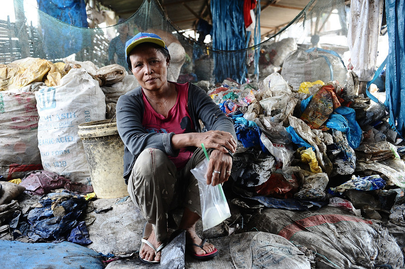 . A woman sits in the middle of a pile of garbage on March 7, 2014 in Surabaya, Indonesia. These women work at the landfill site everyday earning an average of USD $2. Millions of Indonesian women are currently living below the poverty line. According to the Indonesia Central Bureau of Statistics in March 2013, the number of poor in Indonesia reached 28.07 million people, and 70 % of them are women. Tomorrow, around the world, International Women\'s day is observed, celebrating the economic, political and social achievements of women past, present and future.  (Photo by Robertus Pudyanto/Getty Images)