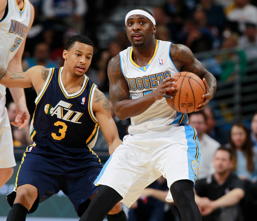 . Denver Nuggets guard Ty Lawson, front, picks up a loose ball as Utah Jazz guard Trey Burke covers in the third quarter of Utah\'s 103-93 victory in an NBA basketball game in Denver on Friday, Dec. 13, 2013. (AP Photo/David Zalubowski)