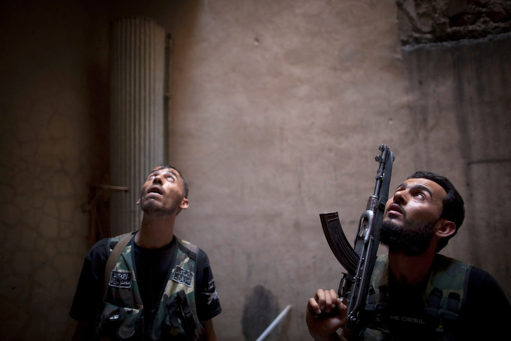 . Rebel fighters look up listening as they take positions during clashes with pro-government forces in the Salaheddine district of the northern Syrian city of Aleppo, on July 9, 2013. JM LOPEZ/AFP/Getty Images