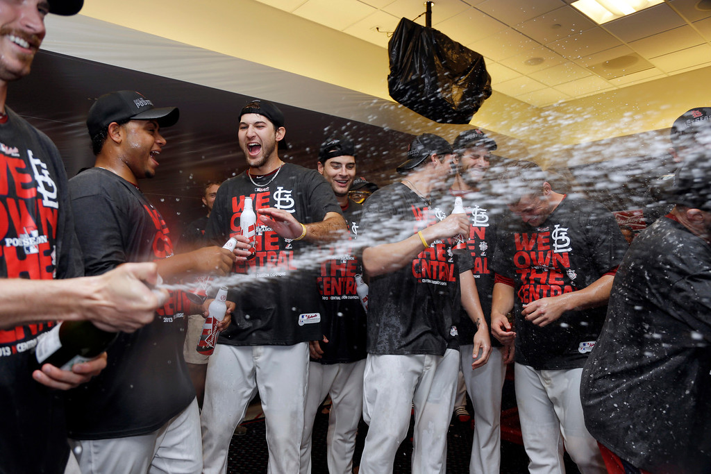 . Members of the St. Louis Cardinals celebrate after a 7-0 win over the Chicago Cubs in a baseball game to clinch the NL Central title Friday, Sept. 27, 2013, in St. Louis. (AP Photo/Jeff Roberson)