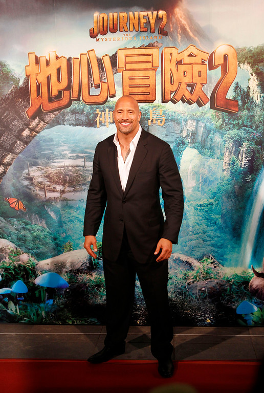 """. American actor Dwayne \""""The Rock\"""" Johnson arrives at the premiere of his new film \""""Journey 2: The Mysterious Island\"""" in Taipei, Taiwan, Wednesday, Jan. 18, 2012. (AP Photo/Wally Santana)"""