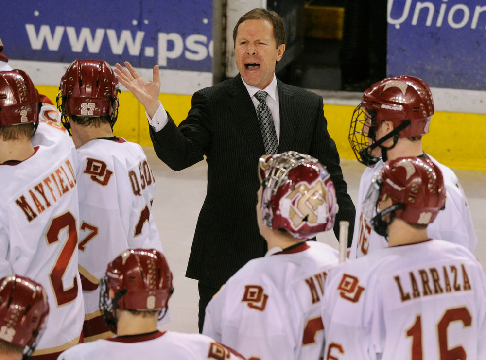 . Denver coach George Gwozdecky tried to get his player to back off the center line following a skirmish at the end of the game.  The University of Denver hockey team defeated Cornell 2-1 at Magness Arena Saturday night, January 5, 2013. Karl Gehring/The Denver Post