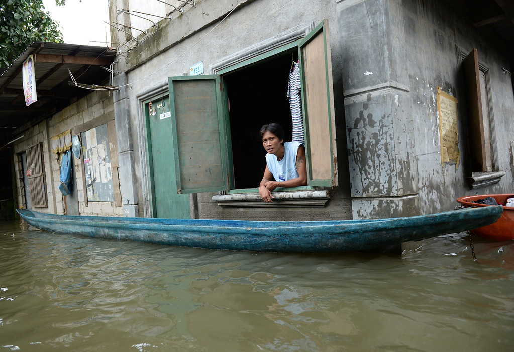 . A man, one of the thousands affected by flooding due to heavy rains exarcebated by Tropical storm Trami, peers from the window of his flooded house while a wooden boat is anchored in the town of Calumpit, Bulacan province, north of Manila on August 22, 2013. Disaster-weary Philippine residents mopped up August 22 after four days of rains that officials said had killed 18 people and forced more than half a million from flooded homes. TED ALJIBE/AFP/Getty Images