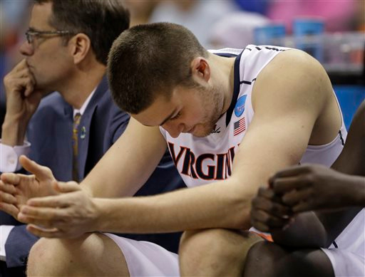 . Virginia\'s Mike Tobey sits on the bench in the final moments during the second half of an NCAA tournament college basketball game against Michigan State in the Round of 32 in Charlotte, N.C., Sunday, March 22, 2015. Michigan State won 60-54. (AP Photo/Gerald Herbert)