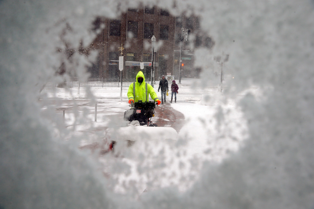 . A worker uses a snowblower to clear a walkway during a snowstorm, Tuesday, March 13, 2018, in Boston. (AP Photo/Michael Dwyer)