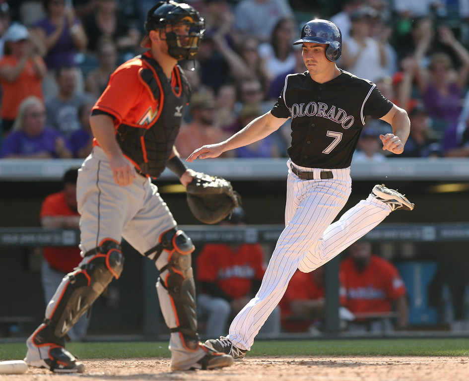 . Miami Marlins catcher Jeff Mathis, leftt, waits for throw as Colorado Rockies\' Matt McBride scores on a double hit by DJ LeMahieu in the seventh inning of the Rockies\' 7-4 victory in a baseball game in Denver on Sunday, Aug. 24, 2014. (AP Photo/David Zalubowski)