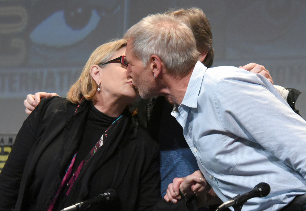 """. FILE - In this July 10, 2015, file photo, Carrie Fisher, left, and Harrison Ford kiss at the Lucasfilm\'s \""""Star Wars: The Force Awakens\"""" panel on day 2 of Comic-Con International in San Diego, Calif. Fisher revealed in an interview with People magazine published online on Nov. 15, 2016, that she had an affair with Ford during the filming of the 1977 film, \""""Star Wars.\"""" (Photo by Richard Shotwell/Invision/AP, File)"""