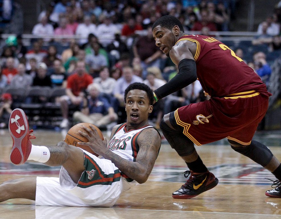 . Milwaukee Bucks\' Brandon Jennings goes to the floor for a loose ball in front of Cleveland Cavaliers\' Kyrie Irving (2) during the first half of an NBA basketball game Wednesday, March 14, 2012, in Milwaukee. (AP Photo/Morry Gash)