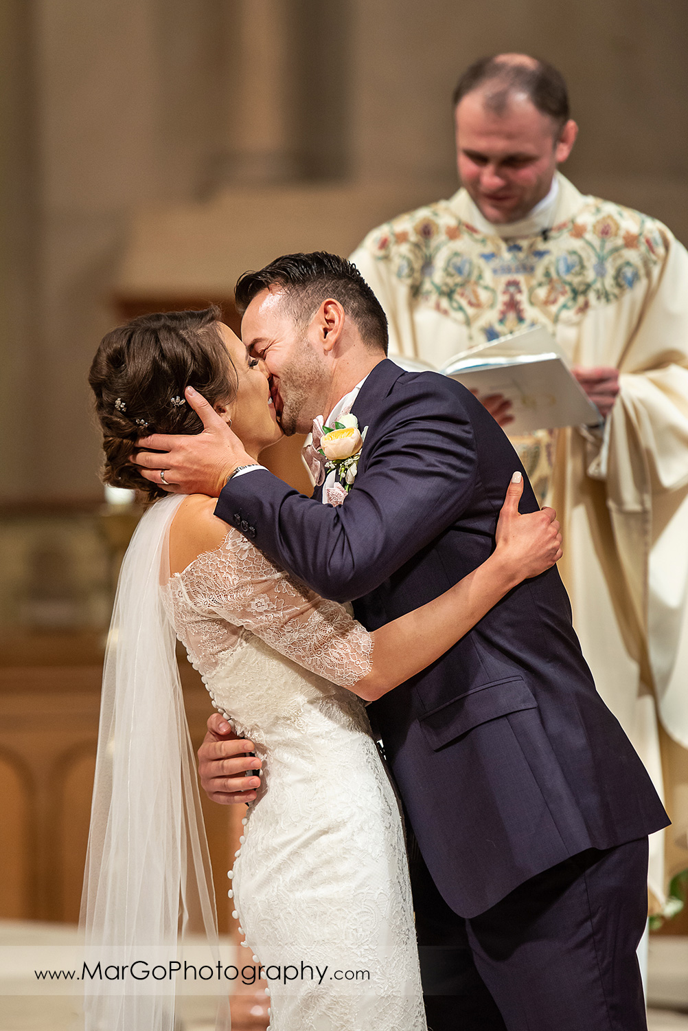 bride and groom kissing during wedding ceremony at Oakland Church of Saint Leo the Great