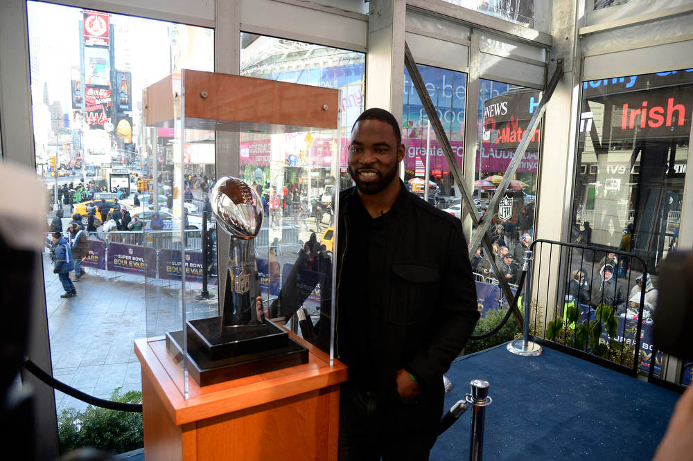 Description of . New York Giants Justin Tuck poses with the Super Bowl Trophy in Times Square. Super Bowl XLVlll fans hit Times Square to enjoy the Super Bowl Boulevard. The NFL transformed a portion of Broadway into the sports and entertainment hub of Super Bowl Week, January 29, 2014. (Photo by John Leyba/The Denver Post)