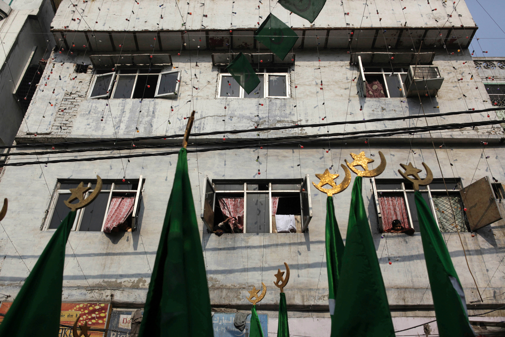 . Indians watch a procession during Eid-e-Milad, the festival that commemorates the birth anniversary of Prophet Muhammad, in New Delhi, India, Tuesday, Jan. 14, 2014. (AP Photo/Tsering Topgyal)