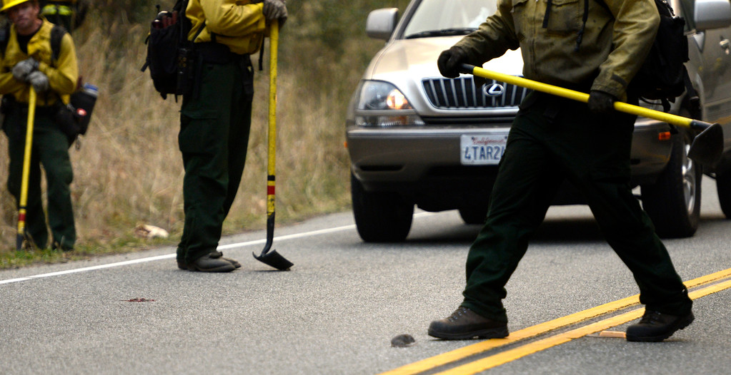 . Firefighters try to help a mouse get across Highway 1 to escape a backfire along Highway 1 between Pfeiffer Ridge Road and the Big Sur Station in Big Sur, Calif. on Wednesday December 18, 2013. (Photo David Royal/ Monterey County Herald)