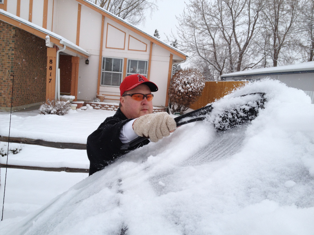 . Craig Sherriff of Arvada cleans off his car after an over night snow fall left 3 to 6 inches across Denver and the surrounding areas February 21, 2013. Arvada, Colorado. (Photo By Joe Amon/The Denver Post)