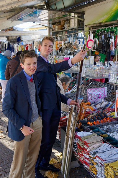 Jack and Dylan looking at a walking cane at the Arona market in Italy