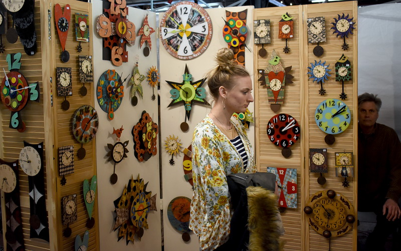 Stephanie Hill, Royal Oak, checks out the wood clocks made by artist Duane Scherer, Lathrup Village.   Visitors browse the jewelry, ceramics, glass, painting, sculpture and other works of 60 juried artists at the 2nd annual Spring Art Fair at the Farmers Market in Royal Oak, Michigan on April 5, 2018. Hosted by The Guild of Artists and Artisans, the event, which runs Friday April 6 from noon to 10pm, kicks off the Art Fair season and includes music, food trucks and craft beverages. Officials expect roughly 7,000 people to attend the 2-day event.  (Photo by Brandy Baker)