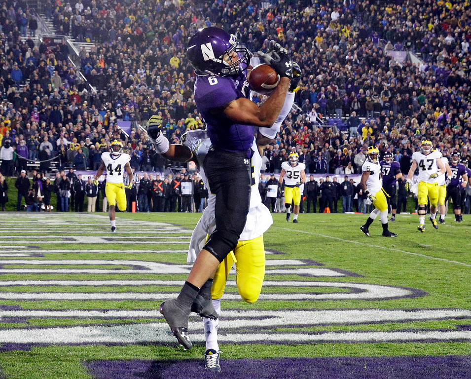. Northwestern wide receiver Tony Jones (6) catches the touchdown pass against Michigan defensive back Delonte Hollowell (24) during the second half of an NCAA college football game in Evanston, Ill., Saturday, Nov. 8, 2014. Michigan won 10-9. (AP Photo/Nam Y. Huh)