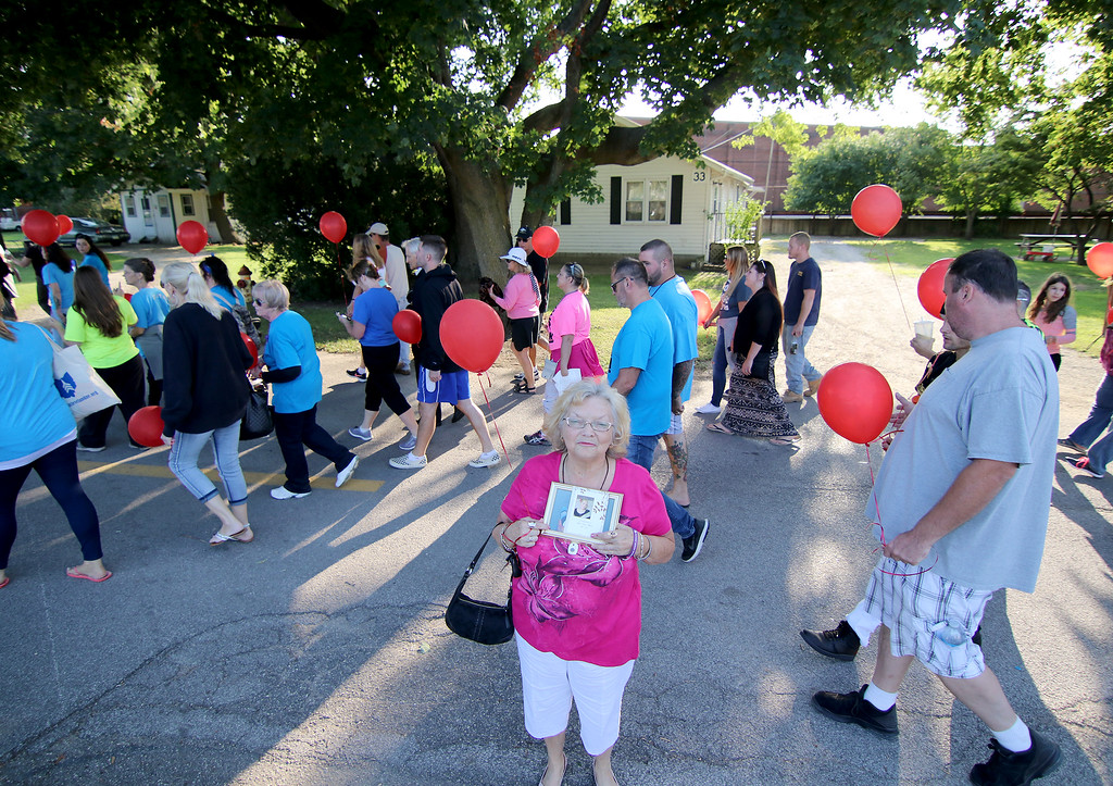 . Jonathan Tressler - The News-Herald. An unidentified participant in the prayer march/memorial at the start of the two-day Hope Over Heroin Lake County event holds a photo of her daughter, also unidentified, she said died a heroin-related death last week.
