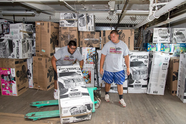 07/11/19 Wesley Bunnell | Staff Ronnie Palma, L and Tyler Ounthongdy, both New Britain Parks and Rec employees, stack toy cars inside of a warehouse at 1 Hartford Square on Thursday morning. Approximately 300 toy cars were donated and delivered by Fisher-Price on to expand the Go Baby Go! program which is a learning project between New Britain High School and CCSU students in the technology fields. The program helps children with limited mobility by modifying toy cars for the exact needs of each child.