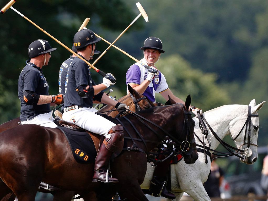 . Britain\'s Prince William (R) rides onto the pitch with the opposing team at the start of the Jerudong Trophy polo match at Cirencester Park Polo Club near Cirencester in central England July 14, 2013. REUTERS/Luke MacGregor