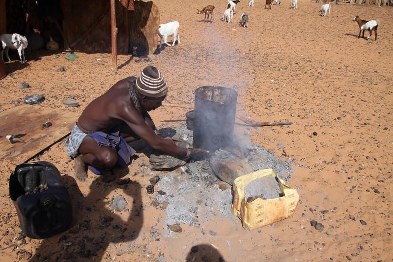 Himba headman cooking a goat