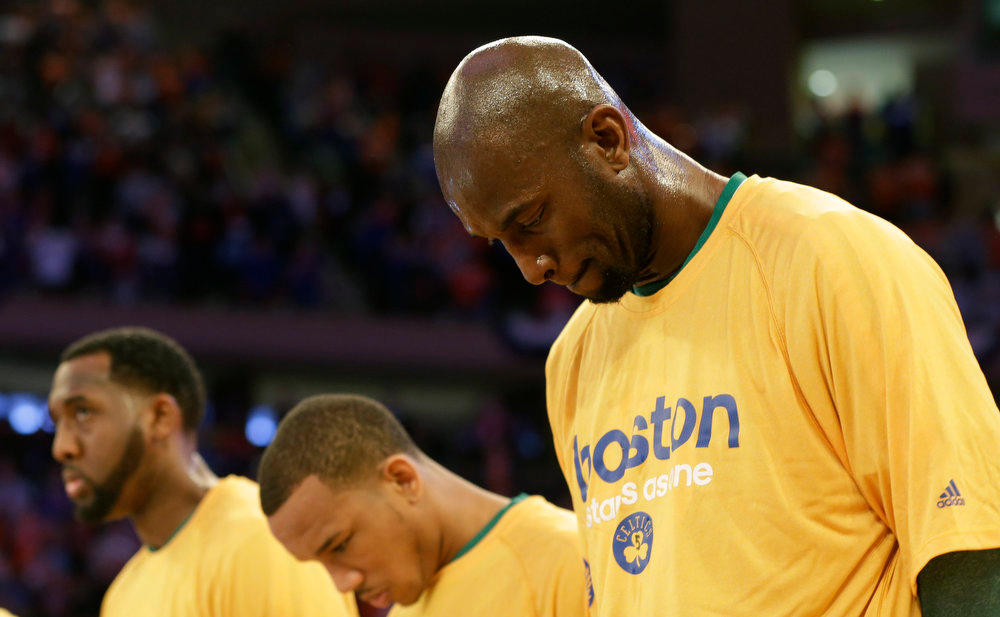 . Boston Celtics center Kevin Garnett. right, and teammates bow their heads during a moment of silence for those injured and killed in the Boston Marathon bombings before the start of Game 1 of an NBA playoff basketball game against the New York Knicks at Madison Square Garden in New York, Saturday, April 20, 2013.  (AP Photo/Kathy Willens)
