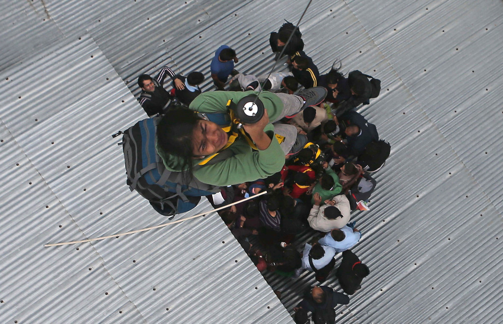 . A tourist is airlifted from the roof of a of a five-story hotel, four of which are submerged in floodwaters, in Srinagar, India, Tuesday, Sept. 9, 2014. (AP Photo/Dar Yasin)