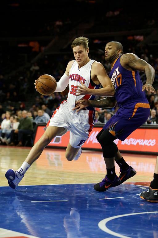 . Detroit Pistons forward Jonas Jerebko (33) of Sweden drives on Phoenix Suns forward P.J. Tucker (17) during the first half of an NBA basketball game in Auburn Hills, Mich., Wednesday, Nov. 19, 2014. (AP Photo/Carlos Osorio)