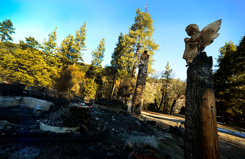. A ceramic angel statue overlooks the burned out cabin which is all that remains of fugitive Christopher Dorner\'s last stand in Seven  Oaks February 15, 2013.   (Photo by Gabriel Luis Acosta/The Sun)
