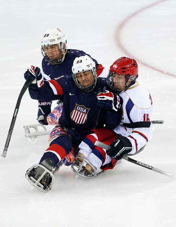 . Rico Roman of USA (C) clashes with Andrey Dvinyaninov of Russia (R) during the Ice Sledge Hockey Preliminary Round Group B match between USA and Russia at the Shayba Arena during day four of the Sochi 2014 Paralympic Winter Games on March 11, 2014 in Sochi, Russia.  (Photo by Harry Engels/Getty Images)