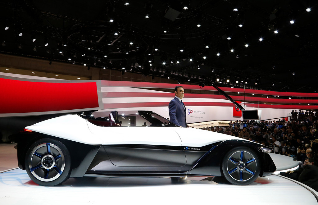 . Nissan Motor Co. President and CEO Carlos Ghosn poses with a Nissan BladeGlider concept car at the media preview for the Tokyo Motor Show at Tokyo Big Sight in Tokyo, Wednesday, Nov. 20, 2013.  (AP Photo/Shuji Kajiyama)