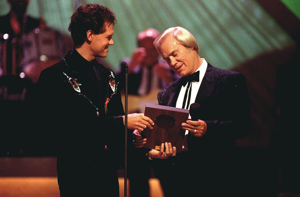 . Country music legend George Jones accepts his Country Music Hall of Fame award from Randy Travis, left, during the Country Music Association Awards show in this Sept. 30, 1992 photo from Nashville, Tn. (AP Photo/Mark Humphrey)