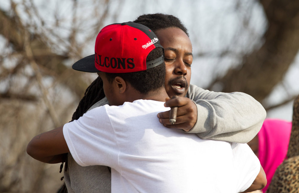 . Leaman Joe, left, hugs Michael Parker, at the crash site that killed their friends on Park Ave. in Warren, Ohio on Sunday, March 10, 2013. (AP Photo/Scott R. Galvin)