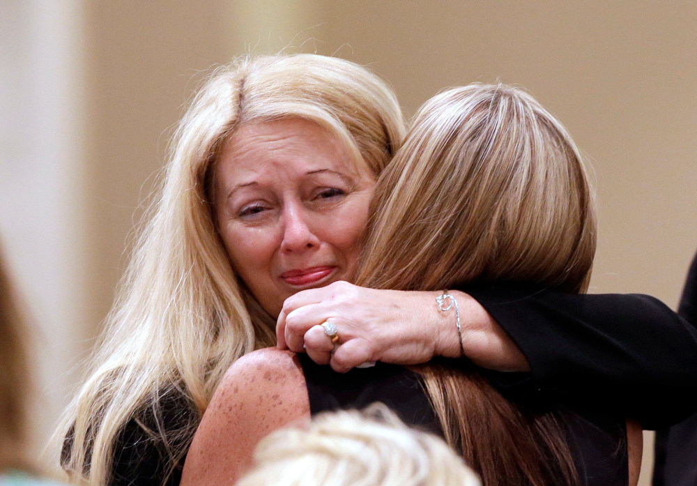 Description of . Gayle Inge, left, is embraced during the funeral ceremony for her daughter, country music star Mindy McCready, at the Crossroads Baptist Church in Fort Myers, Fla., on Tuesday, Feb. 26, 2013.  McCready committed suicide on Feb. 17 at her home in Arkansas, days after leaving a court-ordered substance abuse program. (AP Photo/Alan Diaz)