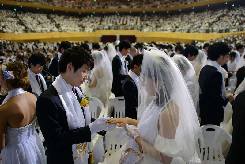 ". A groom puts a ring on the finger of his bride as they are married during a mass wedding event held by the Unification Church in Gapyeong on February 12, 2014. Unification Church members forming 2500 couples from 52 countries were married in a mass wedding in South Korea -- only the second such event since the death of their ""messiah\"" and controversial church founder Sun Myung Moon. (ED JONES/AFP/Getty Images)"
