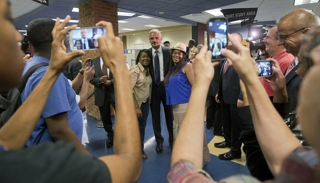 ". FERGUSON, MO - AUGUST 20:  U.S. Attorney General Eric Holder (C) poses for photographs following his meeting with students at St. Louis Community College Florissant Valley August 20, 2014 in Ferguson, Missouri. Holder is traveling to Ferguson, Mo., to oversea the federal government\'s investigation into the shooting of 18-year-old Michael Brown by a police officer on Aug. 9th. Holder promised a ""fair and thorough\"" investigation into the fatal shooting of a young blackman, Michael Brown, who was unarmed when a white police officer shot him multiple times. (Photo by Pablo Martinez Monsivais-Pool/Getty Images)"