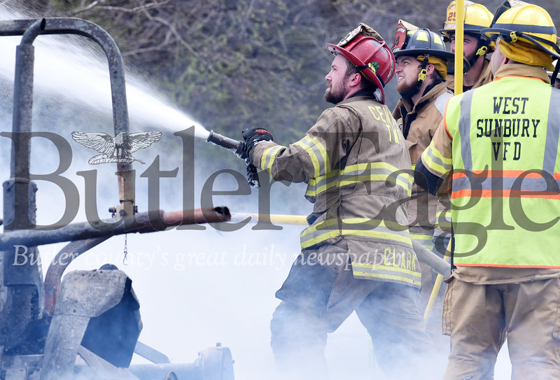 Harold Aughton/Butler Eagle: Firefighter Zach Clark of the Unionville battles a barn fire at 455 West Sunbury Road, Monday, April 15.