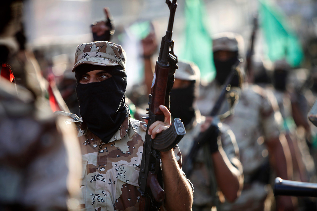 . Masked Palestinian members of the Ezz Al-Din Al Qassam brigade, the military wing of Hamas, carry their weapons while chanting slogans during a parade to mark the anniversary of a battle against Israel in Gaza City, Thursday, Nov. 14, 2013.  (AP Photo/Adel Hana)