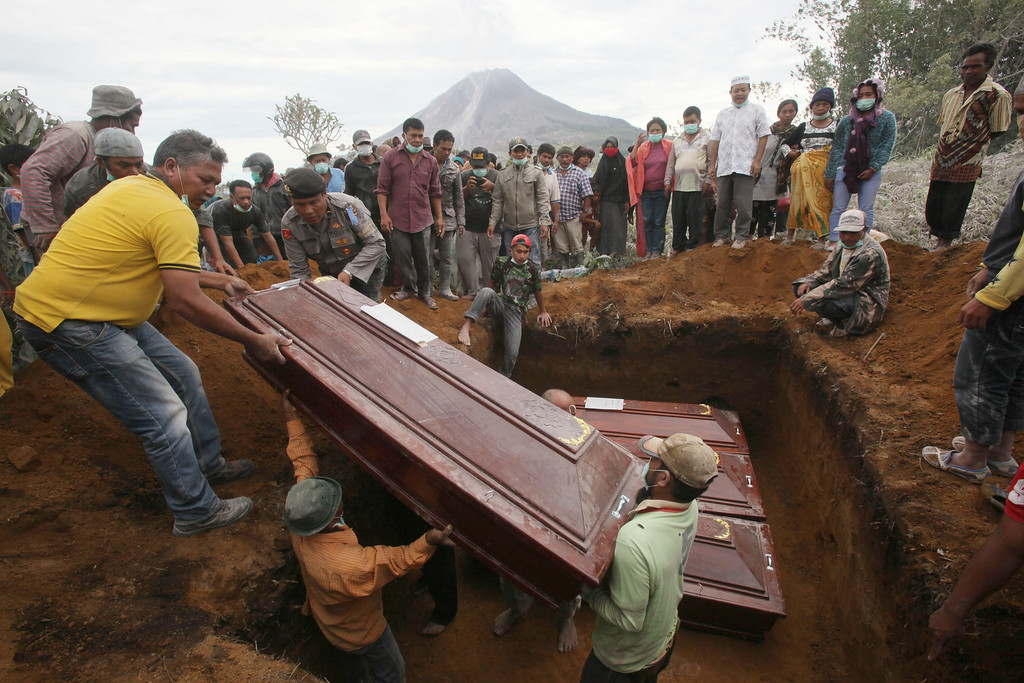 . Coffins containing the bodies of the victims in the eruption of Mount Sinabung are lowered into a grave during a funeral in Sukandebi, North Sumatra, Indonesia, Sunday, May 22, 2016. The volcano blasted volcanic ash as high as 3 kilometers (2 miles) into the sky and down the slopes as far as 4.5 kilometers (3 miles), killing several people who were working on their farms. (AP Photo/Binsar Bakkara)
