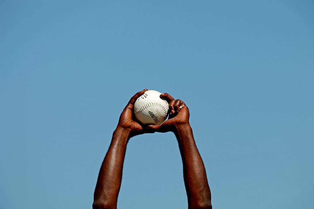 . A pitcher holds up the the ball which beeps before throwing to a batter in blind baseball game in Albany, Ga. on May 5, 2012. Players use their sense of sound to make up for their lack of sight. (AP Photo/David Goldman)