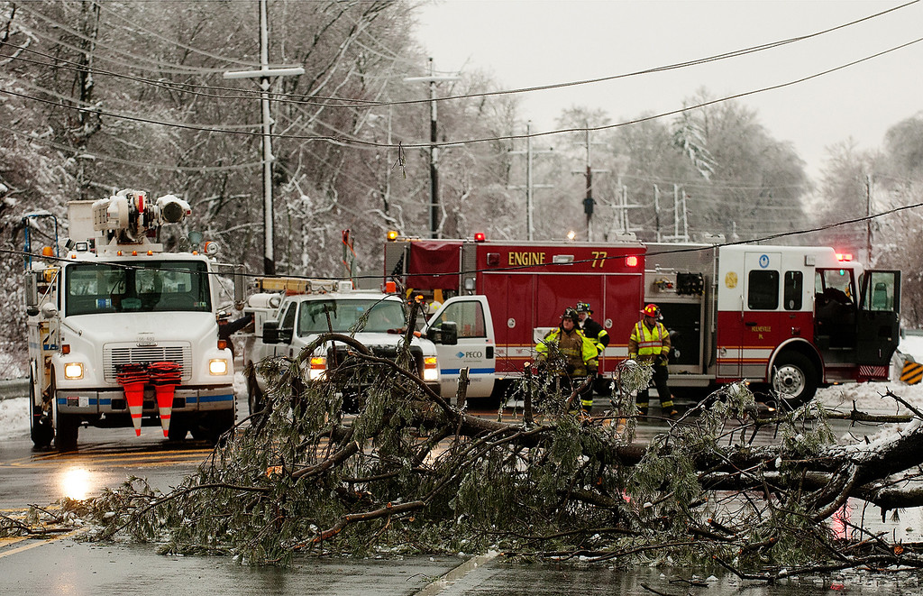 . Emergency personnel prepare to clear a fallen tree from Trenton Road in Middletown Township near Levittown, Pa., Wednesday morning, Feb. 5, 2014. Wednesday knocked out power to more than 560,000 electric customers in eastern and central Pennsylvania and prompted school closures, legislative delays and speed reductions on major roadways. (AP Photo/Bucks County Courier Times, Bill Fraser)