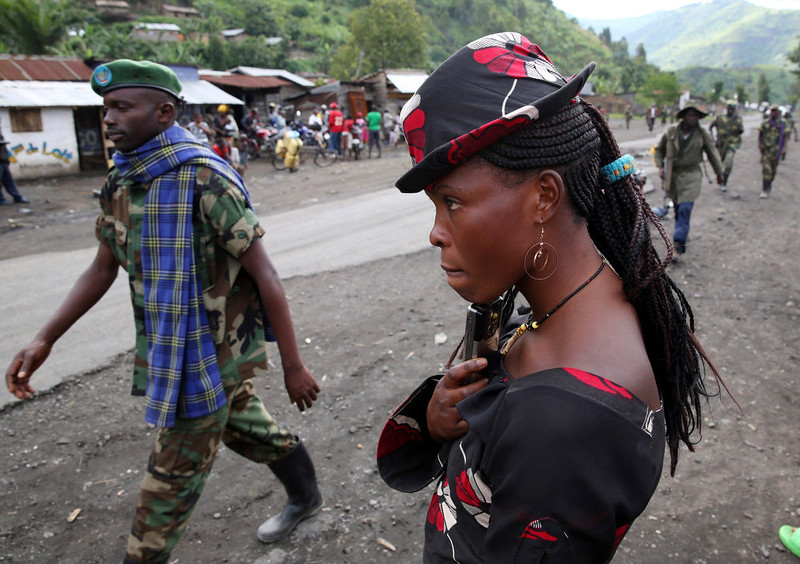 . A M23 rebel fighter walks past a resident as they withdraw from the town of Sake, some 27 km (17 miles) west of Goma November 30, 2012. A rebel pullback from Goma, seized by M23 from fleeing United Nations-backed government forces on November 20, would signal some progress in international efforts to halt the eight-month-old insurgency in eastern Democratic Republic of Congo. REUTERS/Goran Tomasevic