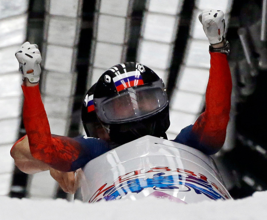 . The team from Russia RUS-1, piloted by Alexander Zubkov and brakeman Alexey Voevoda, cross into the finish area to win the gold medal during the men\'s two-man bobsled competition at the 2014 Winter Olympics, Monday, Feb. 17, 2014, in Krasnaya Polyana, Russia. (AP Photo/Dita Alangkara)