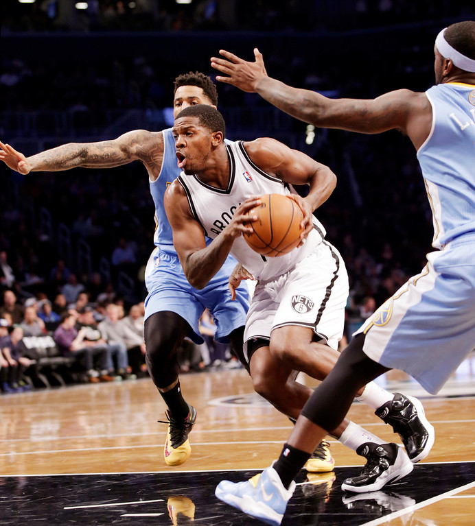. Brooklyn Nets guard Joe Johnson, center, drives past two Denver defenders in the first half of an NBA basketball game Tuesday, Dec. 3, 2013, in New York. (AP Photo/Kathy Willens)
