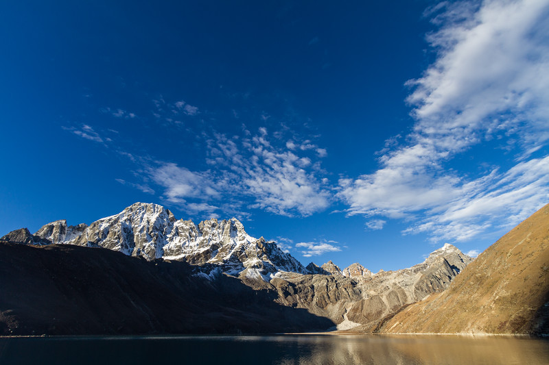 The Machermo Range of Himalayan Mountains is seen reflected in the waters of the third sacred lake at Gokyo, Nepal just after sunrise