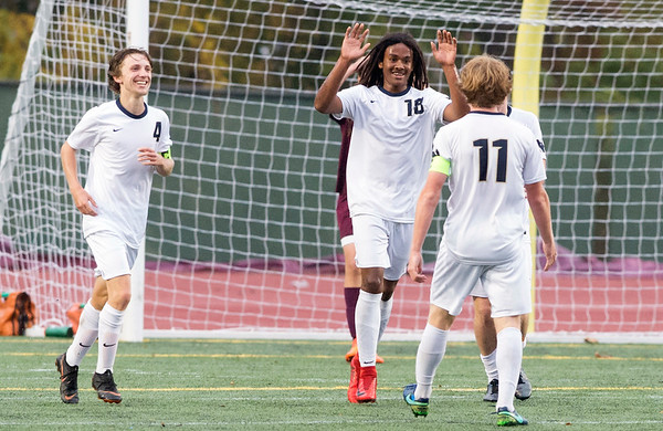 10/29/19 Wesley Bunnell | StaffrrNew Britain soccer was defeated 2-0 by Newington during a drizzle at Veterans Stadium on Tuesday afternoon. Mannasah Dalomba (18) is greeted by teammates after putting Newington up 2-0 in the second half.