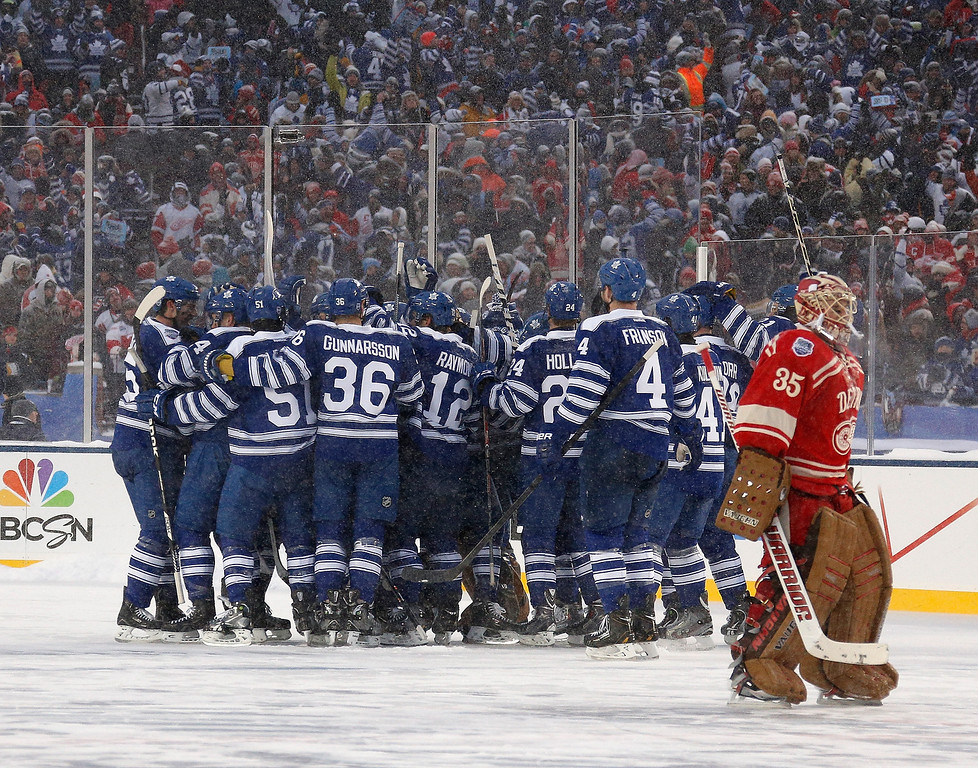 . Jimmy Howard #35 of the Detroit Red Wings skates past the celebrating Toronto Maple Leafs after losing 3-2 in a shootout during the 2014 Bridgestone NHL Winter Classic at Michigan Stadium on January 1, 2014 in Ann Arbor, Michigan. (Photo by Gregory Shamus/Getty Images)